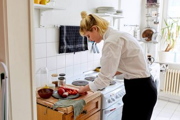 A person standing in a kitchen preparing food